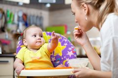 Smiling baby eating food with mom on kitchen Royalty Free Stock Photos