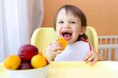 Smiling baby eating fruits Stock Image