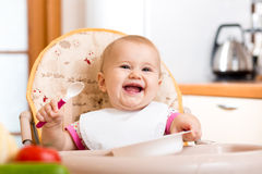 Smiling baby eating on kitchen Royalty Free Stock Image