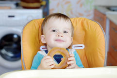 Smiling baby eating round cracknel on kitchen Royalty Free Stock Photography