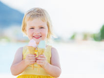 Smiling baby eating two ice cream horns Stock Photos