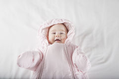 Smiling baby face wrapped in pink snowsuit Royalty Free Stock Images