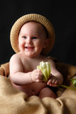 Smiling baby with flower. Portrait of smiling baby boy on hessian sack with straw hat playing with flower, black studio background royalty free stock photo