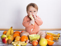 Smiling baby and fruits. Smiling baby eating banana and many kinds of fruit and bowl with yoghurt Stock Photography