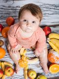 Smiling baby and fruits. Smiling baby eating banana and many kinds of fruit and bowl with yoghurt Stock Image