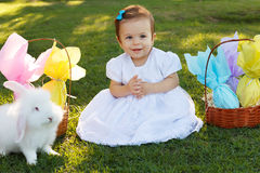 Smiling baby girl with basket with chocolate eggs, white rabbit Royalty Free Stock Images
