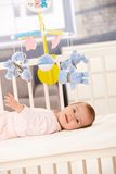 Smiling baby girl in bed stock image