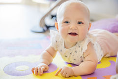 Smiling baby girl with blue eyes playing on floor mate Royalty Free Stock Image