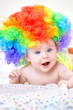 Smiling baby girl with colorful wig Stock Photo