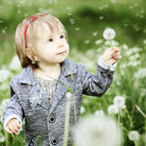 Smiling baby girl with dandelion on grass. Smiling baby girl with dandelion on green grass Stock Images