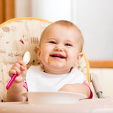 Smiling baby girl eating food on kitchen Royalty Free Stock Images