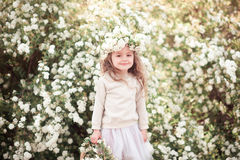 Smiling baby girl with flowers in garden Stock Images
