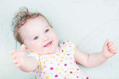 Smiling baby girl on a green blanket Stock Photos