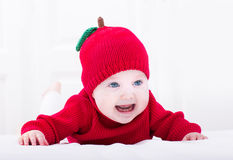 Smiling baby girl on her tummy wearing red apple hat Royalty Free Stock Photography