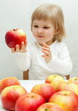 Smiling baby girl holding a ripe  apple Royalty Free Stock Photo