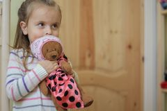 Smiling baby girl holding teddy bear indoors royalty free stock images