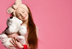 Smiling baby girl holding a white teddy bear in the room a pink backdrop. Isolated Pajama party. Childhood. Playful stock image