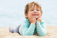 Smiling baby girl laying on  beach Royalty Free Stock Image