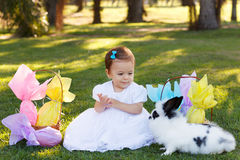 Smiling baby girl looking at rabbit with Easter chocolate eggs Stock Photo