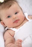 Smiling Baby Girl Lying Down on the Bed Stock Image