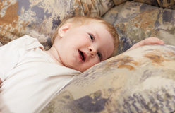 Smiling baby girl lying on a sofa at home Royalty Free Stock Image