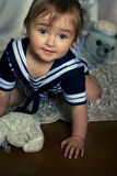Smiling baby girl in the nautical striped vest sits on the carpe Stock Photos