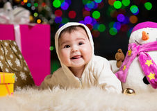 Smiling baby girl near Christmas tree with gifts Stock Photos