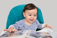 Smiling baby girl with photo album. Cute smiling baby girl looking at the photo album Stock Photos