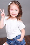 Smiling baby girl posing on gray Royalty Free Stock Image