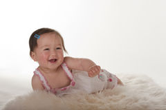 Smiling baby girl on sheepskin rung Stock Photography