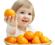The smiling baby girl is showing the tasty tangerine Stock Image