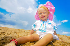 Smiling baby girl sitting on a beach Royalty Free Stock Photo