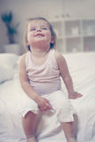 Smiling baby girl sitting on the bed Royalty Free Stock Photo