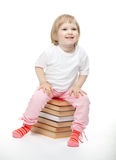 Smiling baby girl is sitting on the books Royalty Free Stock Photography