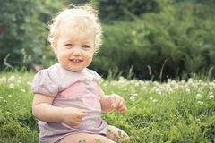 Smiling baby girl sitting in grass among blossoming flowers in summer park in sunny day with copy space Stock Images