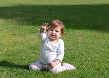 Smiling baby girl sitting on a grass Royalty Free Stock Photos