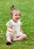 Smiling baby girl sitting on grass at park Stock Photography