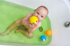 Smiling baby girl taking bath. And playing with toys Royalty Free Stock Photos