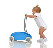 Smiling baby girl toddler with toy walker make first steps Royalty Free Stock Photography