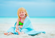 Smiling baby girl in towel sitting on beach Stock Image
