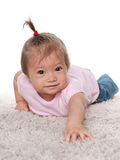 Smiling baby girl on the white carpet Stock Image