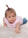 Smiling baby girl on the white carpet Stock Image