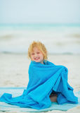Smiling baby girl wraped in towel on beach Stock Photography