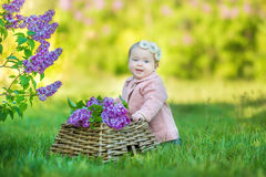 Smiling baby girl 1-2 year old wearing flower wreath, holding bouquet of lilac outdoors. Looking at camera. Summer spring time. Royalty Free Stock Image