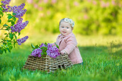 Smiling baby girl 1-2 year old wearing flower wreath, holding bouquet of lilac outdoors. Looking at camera. Summer spring time. Stock Photo