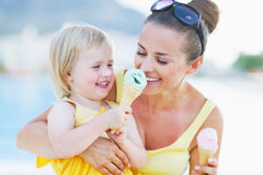 Smiling baby giving mother ice cream Royalty Free Stock Images