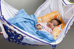Smiling Baby in a Hammock-Style Cradle royalty free stock photos