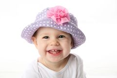 Smiling baby with hat. Smiling baby girl showing teeth wearing a purple polka dot hat with pink flower isolated on white background Stock Photos