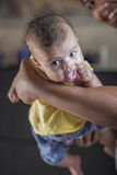 Smiling baby held in the air by her mother Stock Photography