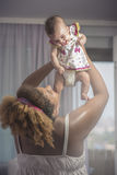 Smiling baby held in the air by her mother Stock Images